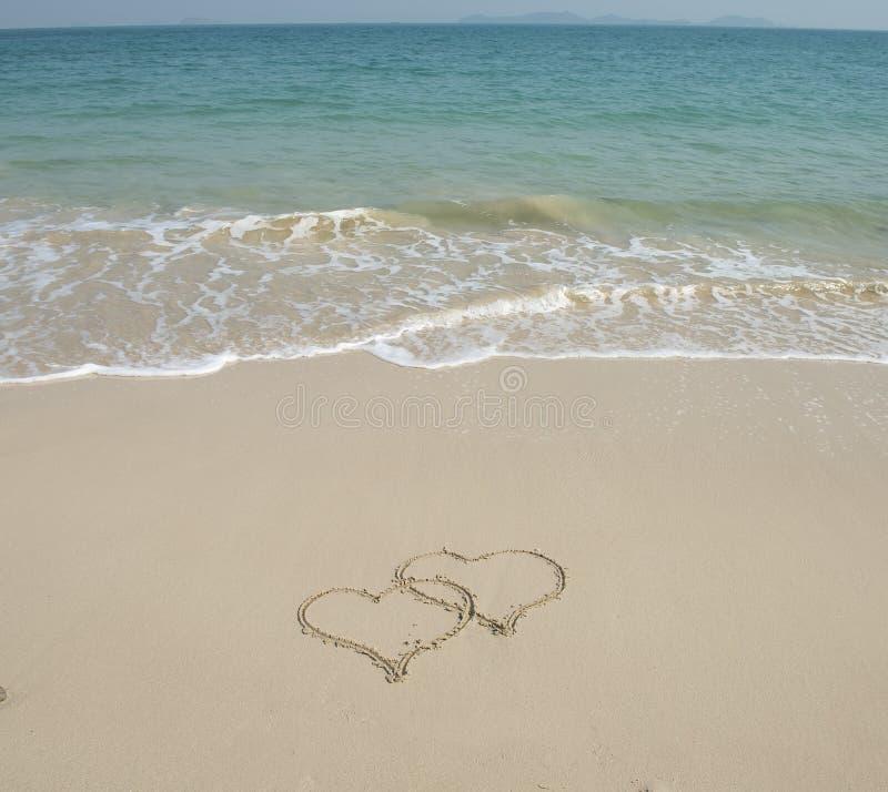 Två hjärtor som tecknas i strand 库存图片