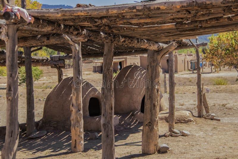 Två hornos-traditionella jord- ugnar under en torkande kugge med en childsdocka som in lämnas på hörnet - hem av Ute Pueblo royaltyfri foto