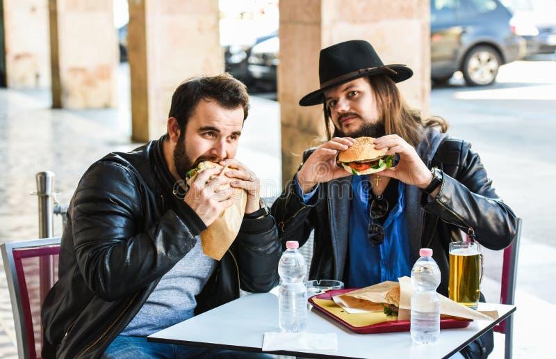 Två hungriga vänner/turister äter hamburgare royaltyfri foto