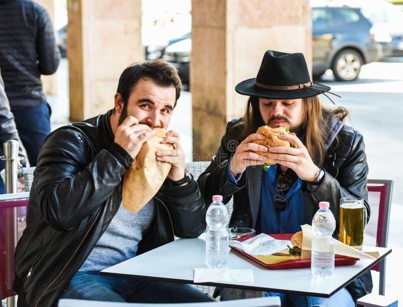 Två hungriga vänner/turister äter hamburgare royaltyfri bild