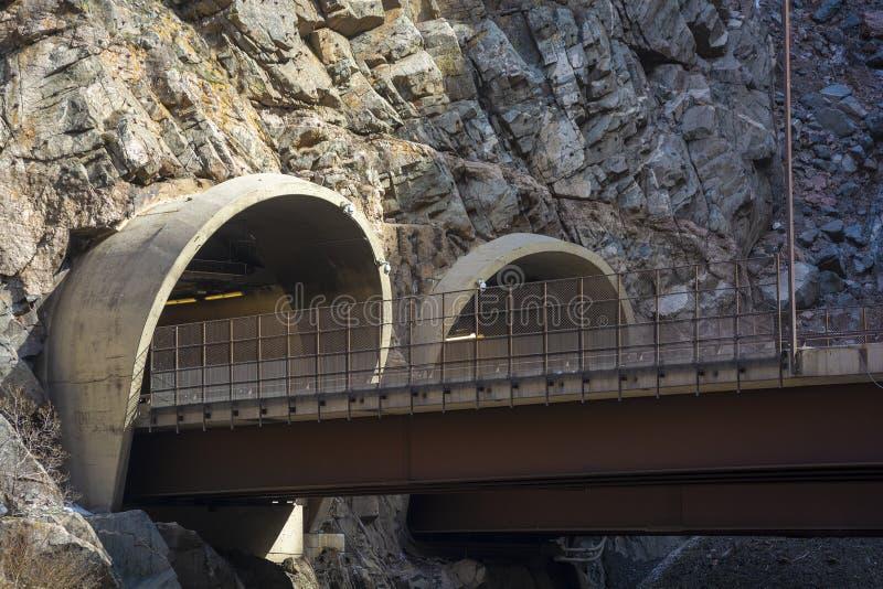 Två huvudvägtunnelingångar klippte in i en bergssida fotografering för bildbyråer