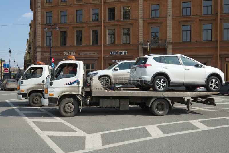 Två Hyundai HD78 bilbärgningsbilar med nedsänkta bilar arkivfoton