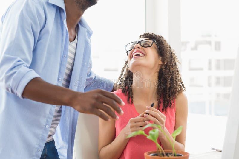 Två idérika affärskollegor som tillsammans skrattar royaltyfri foto