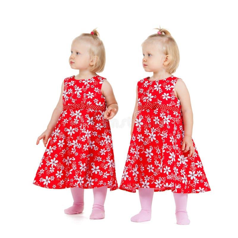 Två identiska tvilling- flickor i rött se för klänningar arkivfoto
