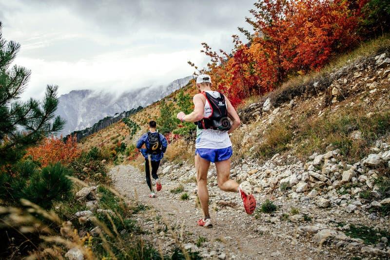 Två idrottsman nenlöpare som kör från berget längs slinga i höstlandskap arkivbilder