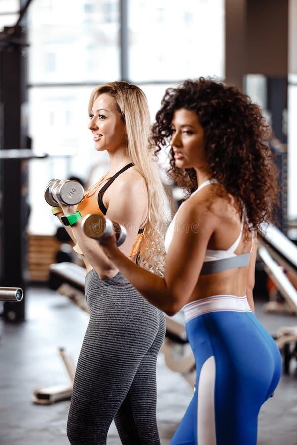 Två iklädda idrotts- flickor en sportswear gör övningar med hantlar i den moderna idrottshallen med det stora fönstret royaltyfria bilder