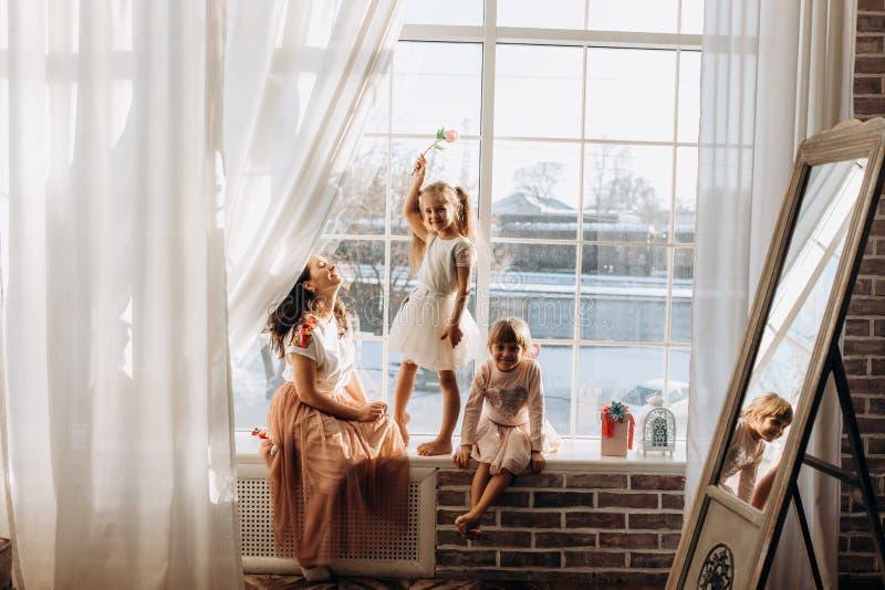 Två iklädda lilla systrar de härliga klänningarna och där ung moder att sitta på fönsterbrädan bredvid den spegeln royaltyfria foton