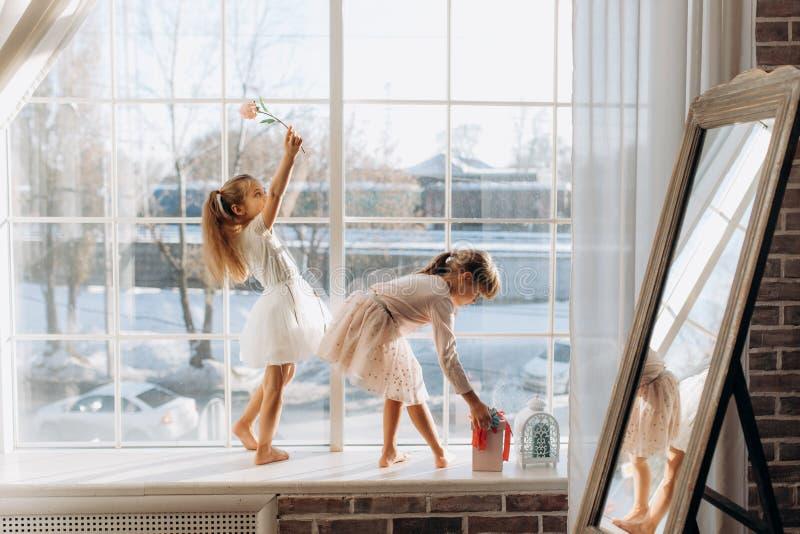 Två iklädda lilla systrar de härliga klänningarna står på fönsterbrädan bredvid spegeln vintern utanför fotografering för bildbyråer