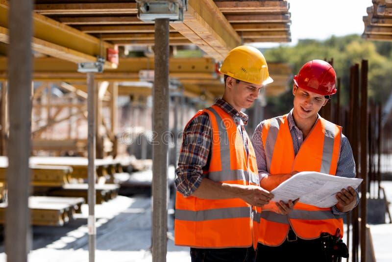 Två iklädda orange arbetsvästar och hjälmar för väg-och vattenbyggnadsingenjör undersöker konstruktionsdokumentation på byggandep arkivbild