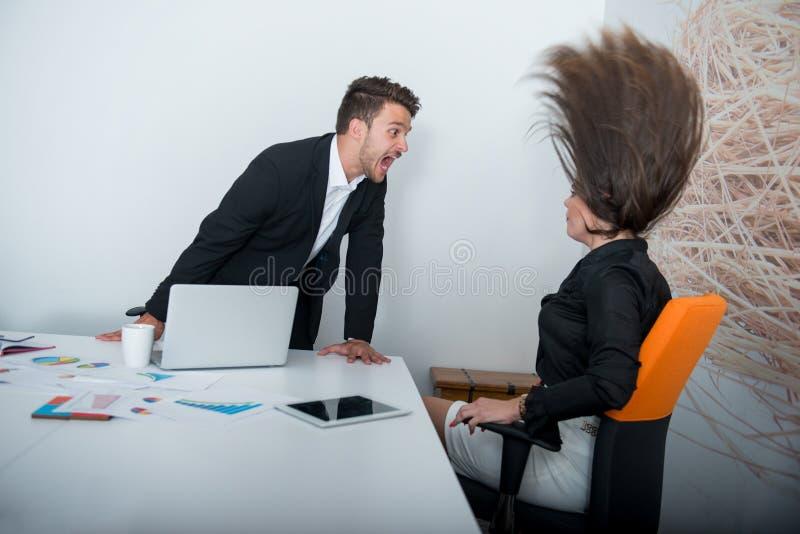 Två ilskna businesspeople som argumenterar rasande visning som en negativ tillväxt graph royaltyfri fotografi