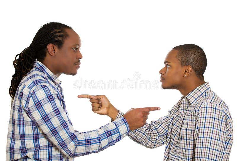 Två ilskna grabbar som pekar fingrar på de och att klandra sig royaltyfria foton
