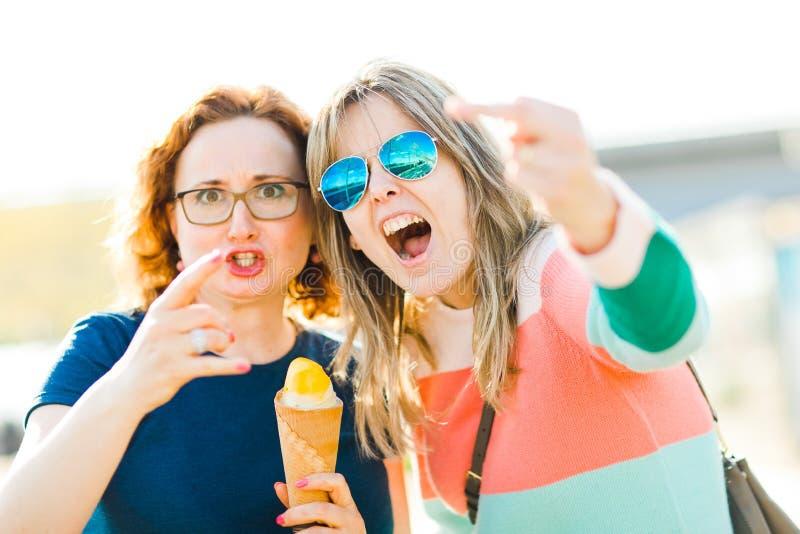 Två ilskna kvinnor som visar obscna gester arkivbilder