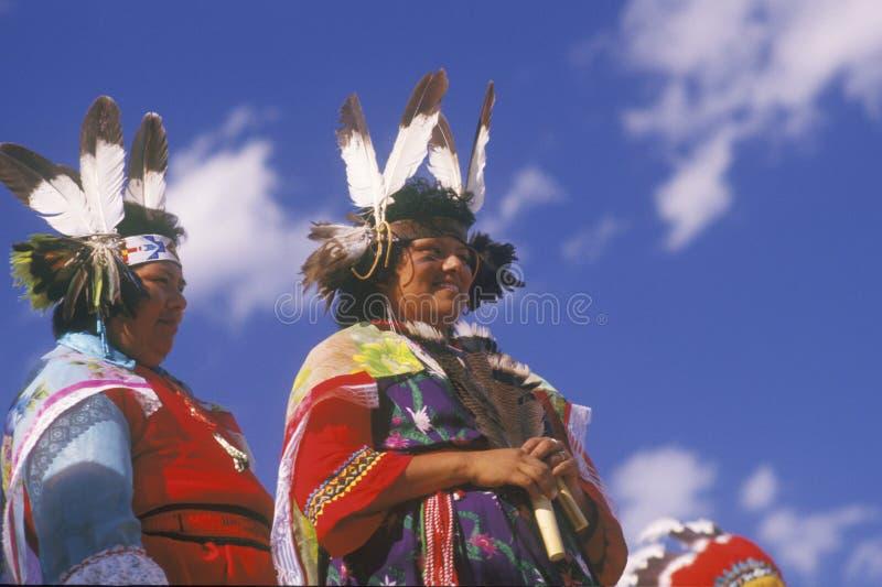 Två indiankvinnor i den traditionella dräkten på ceremonin för havredans, Santa Clara Pueblo, NM fotografering för bildbyråer