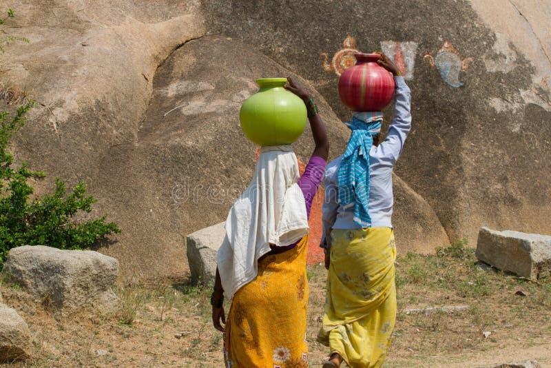 Två indiska kvinnor bär vatten på deras huvud i krukor arkivfoton