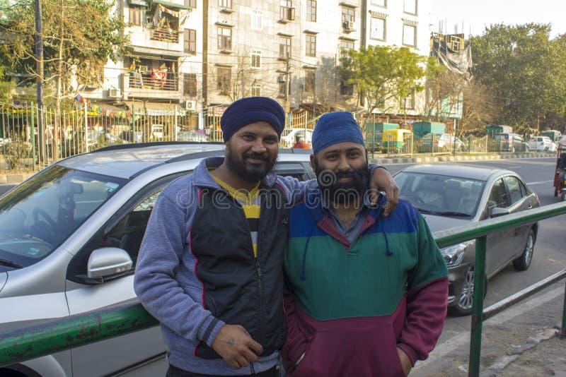 Två indiska skäggiga män i blåa turbaner som kramar mot bakgrunden av stadsvägen royaltyfri fotografi