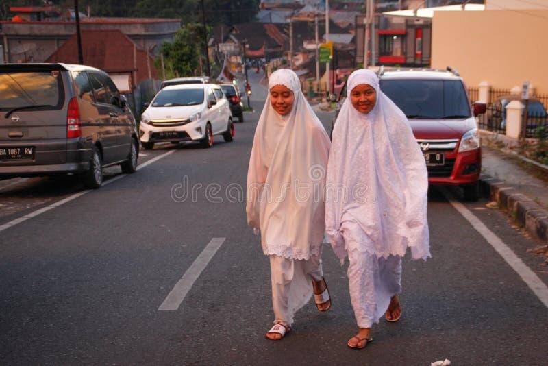 Två indonesiska flickor går på en stadsgata i vit kläder och hijab royaltyfri bild