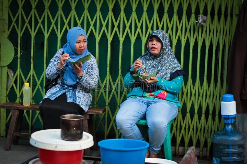 Två indonesiska muslimska kvinnor som äter i Medan, Sumatra, Indonesien arkivfoton