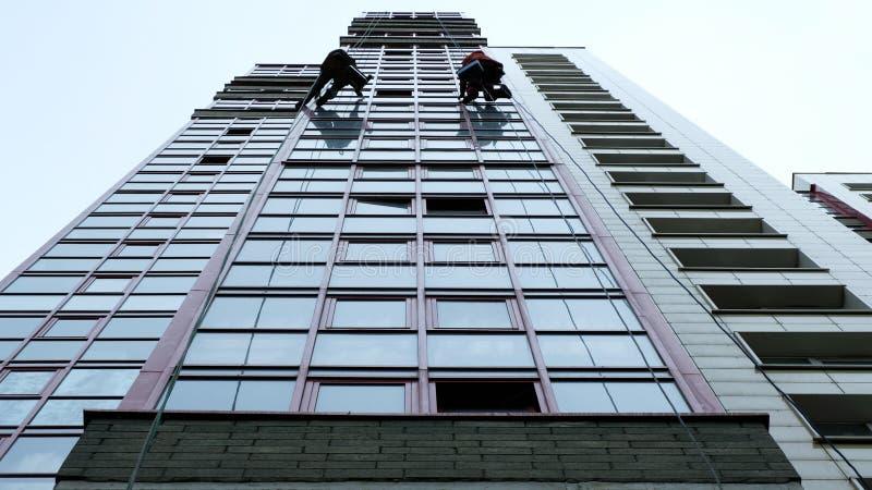 Två industriella klättrare är tvätt som gör ren fasaden av en modern kontorsbyggnad arkivbilder