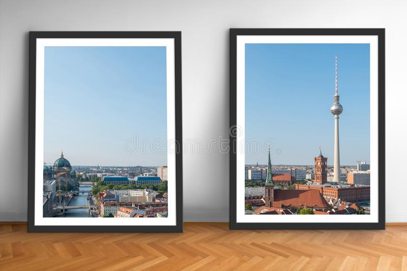 Två inramade bilder av Berlin horisont på vit väggbakgrund för trägolv royaltyfria foton