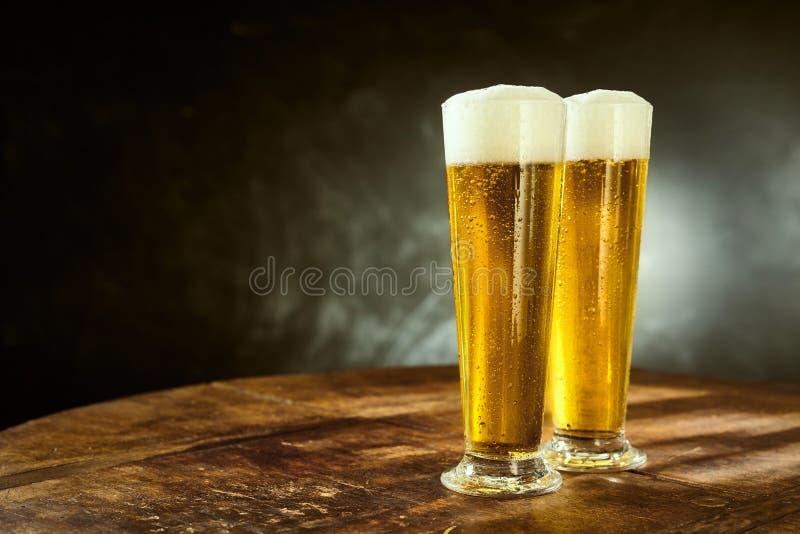 Två iskalla skummiga öl i eleganta långa exponeringsglas arkivbilder