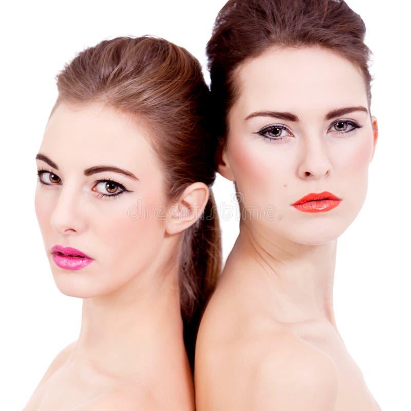 Två isolerade härliga flickor med colorfullmakeup royaltyfri bild