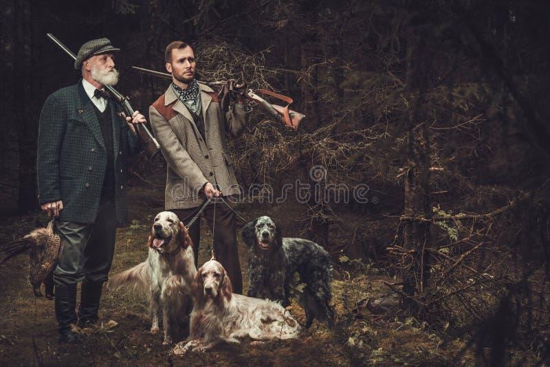 Två jägare med hundkapplöpning och hagelgevär i traditionella skyttekläder som poserar på en mörk skogbakgrund arkivbild