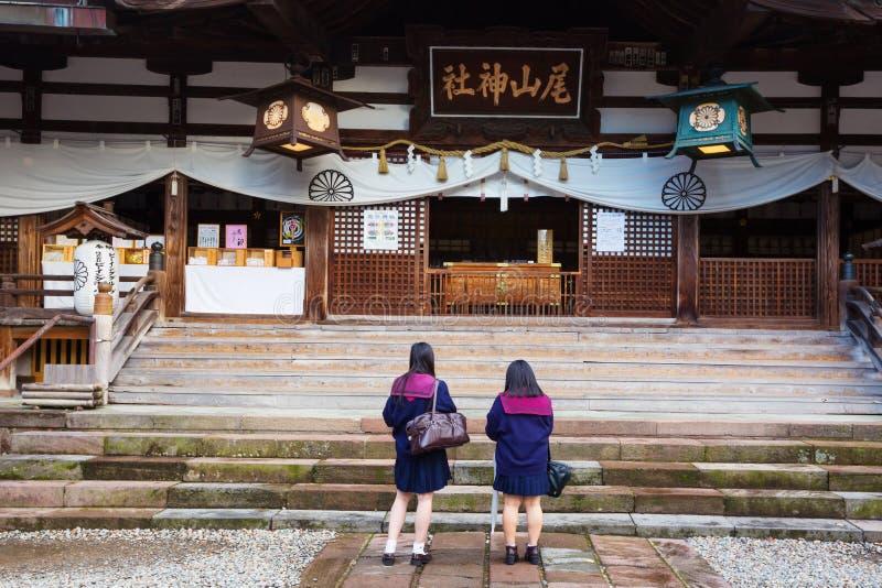 Två japanska skolflickor ber på den Oyama Jinja relikskrin Kanazawa Japan arkivbilder