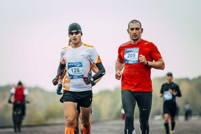 Två joggers för unga män som körs längs invallning arkivbild