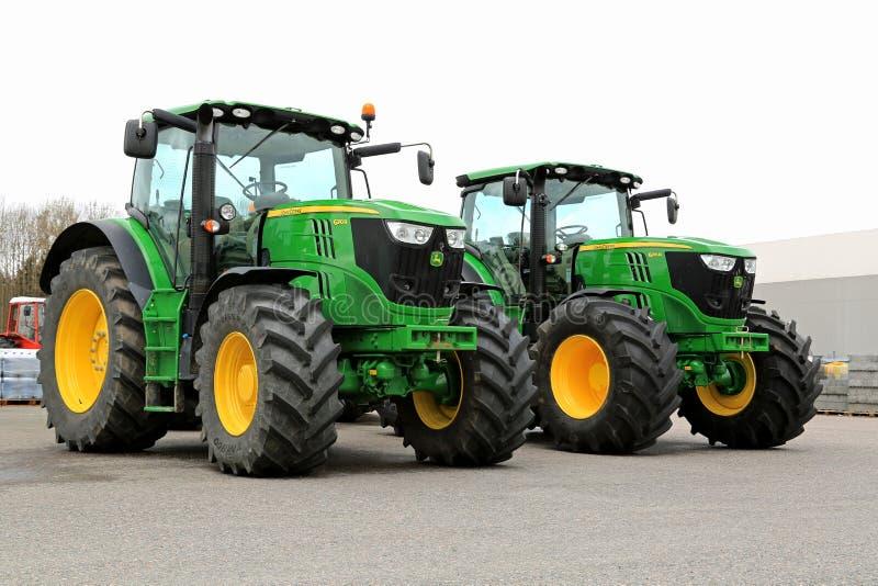 Två John Deere 6210R jordbruks- traktorer på en gård royaltyfri foto