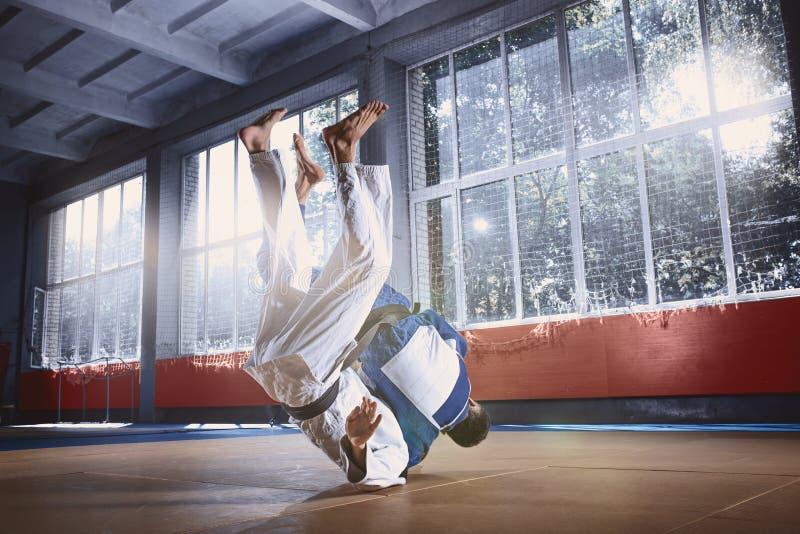 Två judokämpar som visar teknisk expertis, medan öva kampsporter i en kampklubba royaltyfri bild