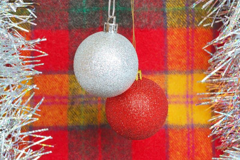 Två julbollar av röda och silverfärger på en bakgrund av tyg för röd-guling ullpläd Begrepp av ferier, jul och N arkivbilder