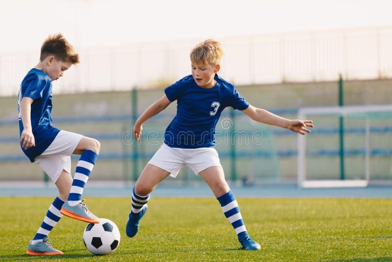 Tv? Junior Soccer Players Training med fotbollbollen p? stadiongr?sgraden fotografering för bildbyråer