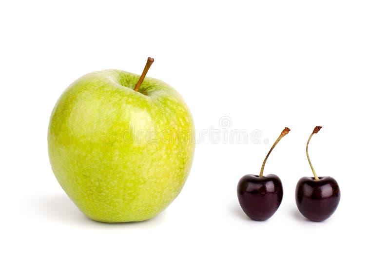 Två körsbärsröda bär och ett stort grönt äpple på vit bakgrund isolerat slut upp makro arkivfoton
