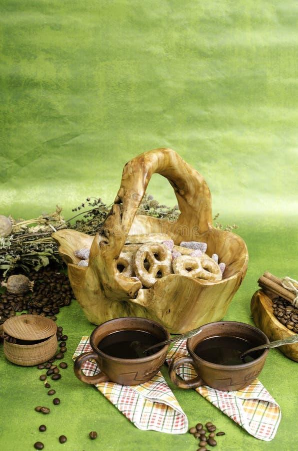 Två kaffe, kakor i korgen som göras av trä, kaffebönor och honom royaltyfri fotografi
