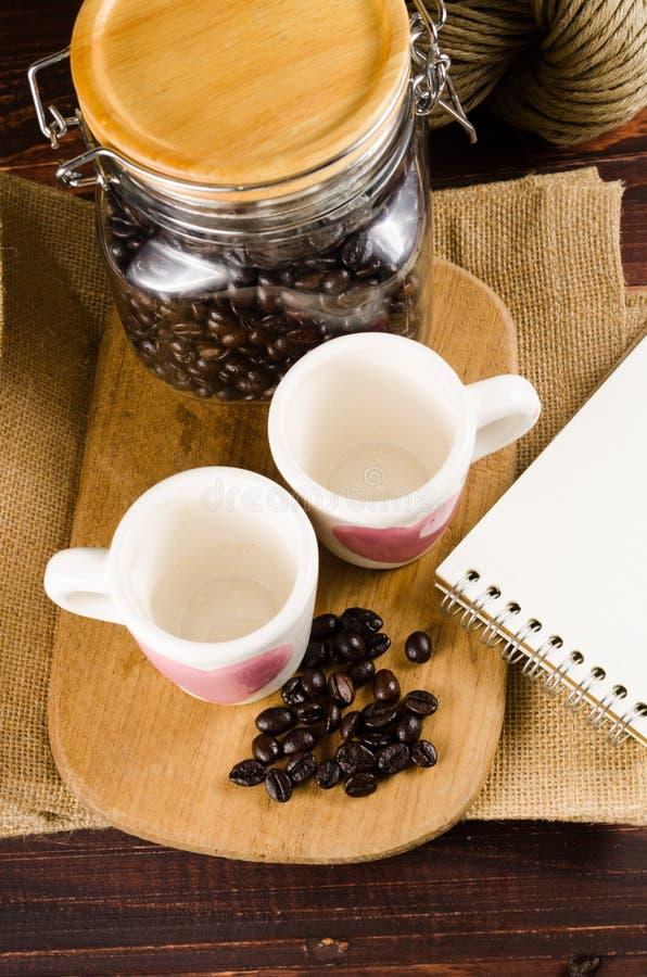 Två kaffekopp på träbräde- och kaffeflaskan med tillbaka backg arkivbilder