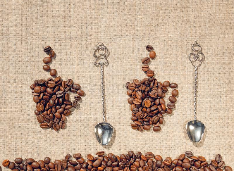 Två kaffekoppar, antikvitetskedar och linne dekorativ bakgrund royaltyfria foton