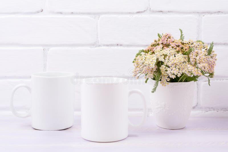 Två kaffesmuggar med rosa beige vilda blommor arkivfoton