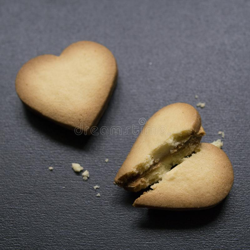 Två kakor i formen av hjärta, ett av dem är brutna på svart bakgrund Knäckt hjärta formade kakan som begrepp av upplösningen royaltyfria bilder