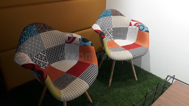 Två kallare, vackra, trädbeklädda stolar sitter ensamma på artificiellt grönt gräs, ser så fredligt och tyst ut att de känner oss arkivbilder