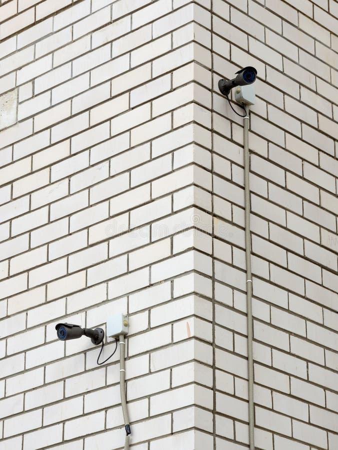 Två kameror som installeras på hörnet av byggnaden fotografering för bildbyråer