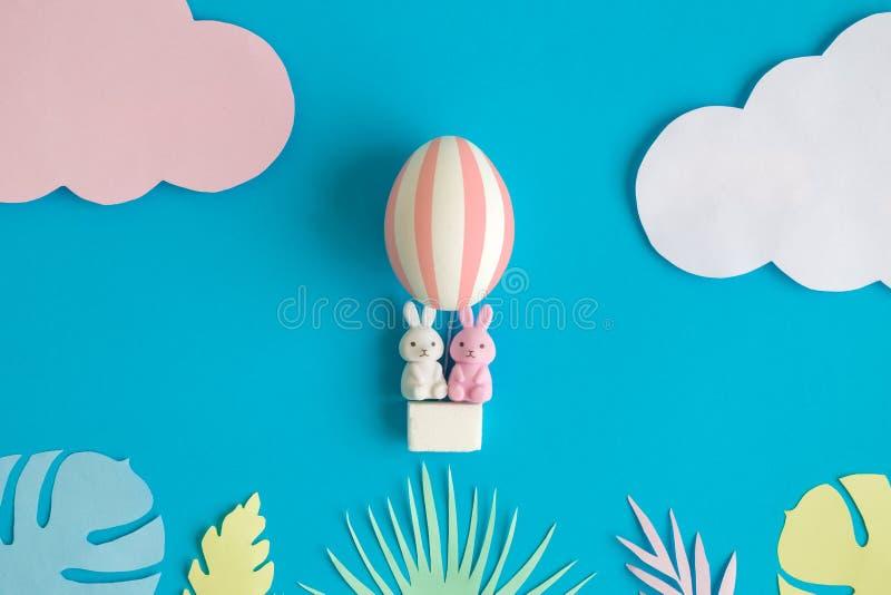 Två kaninleksaker i äggballongen och mångfärgade sidor som göras av papper, easter abstrakt begrepp royaltyfria bilder