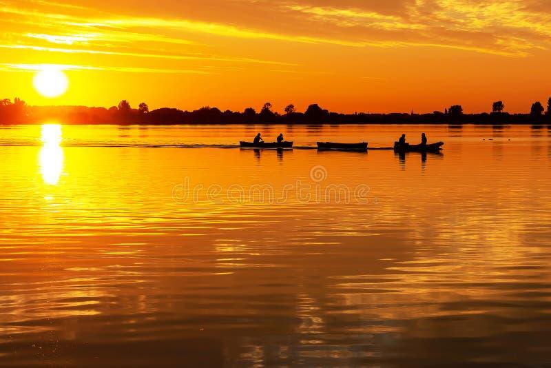 Två kanoter drog vid en motorbåt under härlig solnedgång i sjöZoetermeerse plas royaltyfri bild
