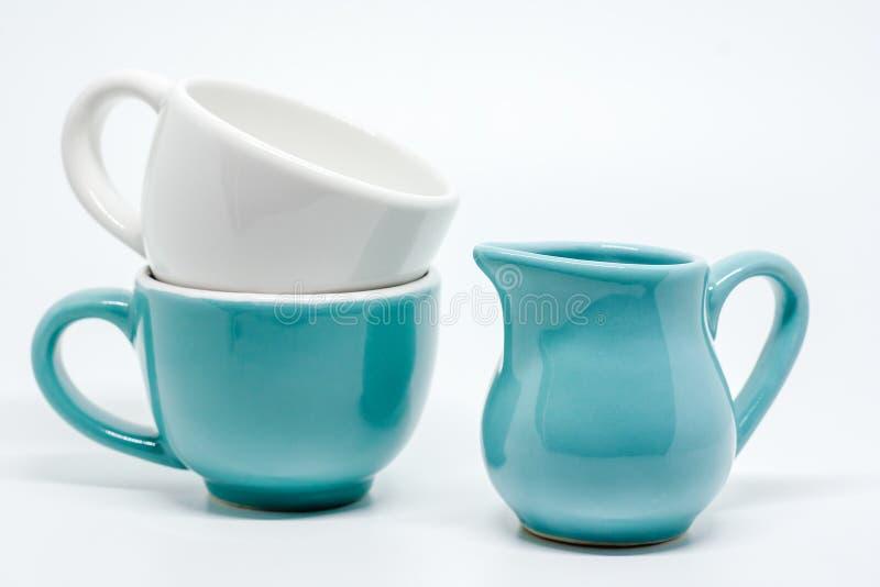 Två keramiska kopp och kanna på vit bakgrund royaltyfria foton