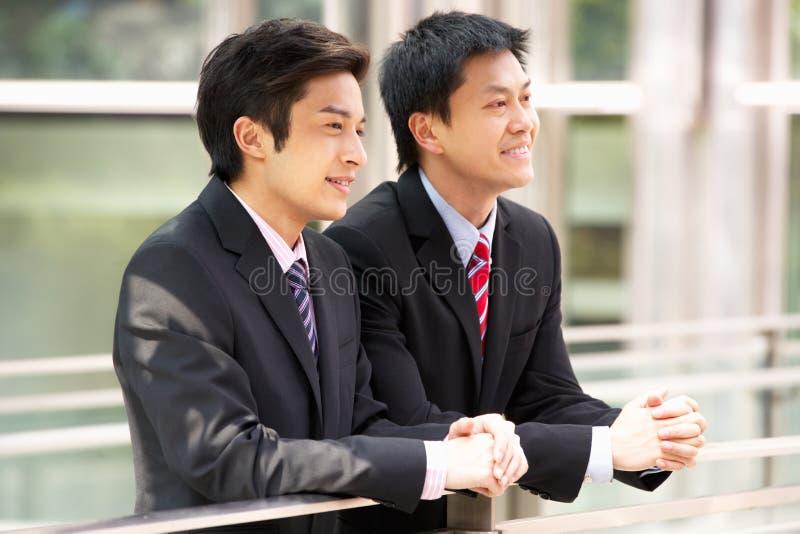 Två kinesiska affärsmän utanför modernt kontor royaltyfri foto