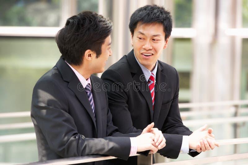 Två kinesiska affärsmän utanför modernt kontor arkivfoto