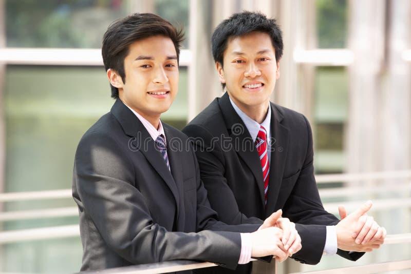 Två kinesiska affärsmän utanför modernt kontor royaltyfri fotografi