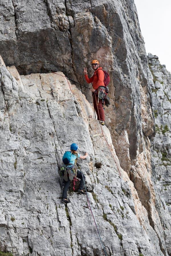 Två klättrare, en man och en kvinna, klättring till överkanten av en vaggaframsida royaltyfri fotografi