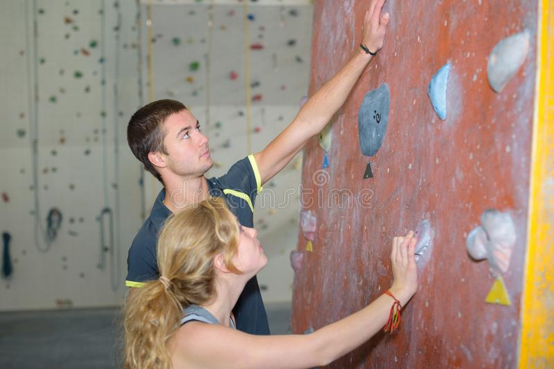 Två klättrare i klättringidrottshall inomhus arkivbilder