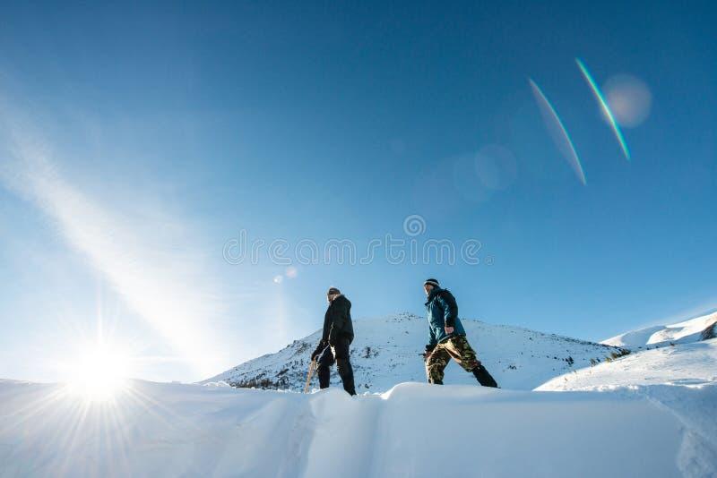 Två klättrare med en isyxa som går i de snöig bergen fotografering för bildbyråer