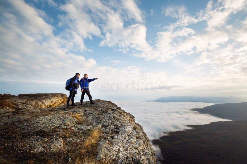 Två klättrare som överst står av ovannämnda moln för toppmöte i bergen Fotvandrareman som pekar med hans hand som diskuterar rutt arkivbild